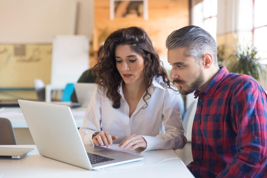 שירותי יעוץ מקצועיים - Serious coworkers discussing project and using laptop together